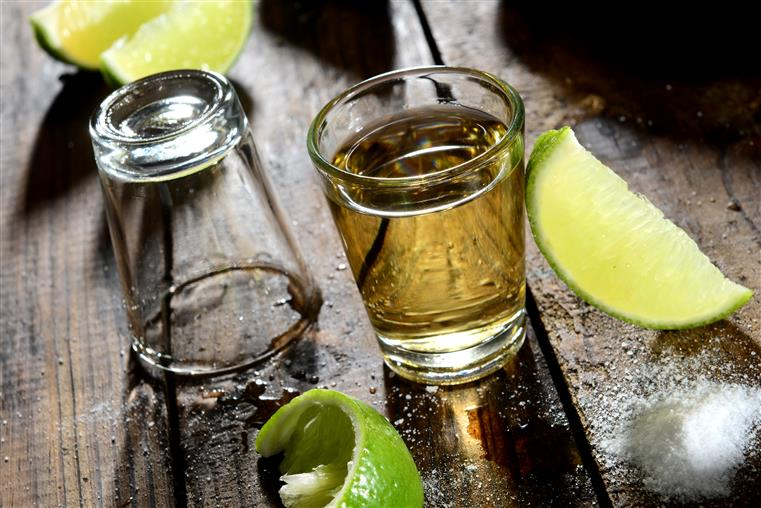 shot glasses with lime wedges