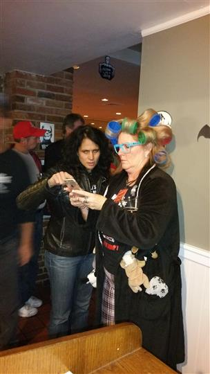 Two women dressed in costume looking at a phone and talking