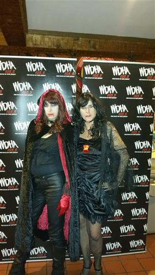 Two women dressed in halloween costumes posing for photo in front of a backdrop
