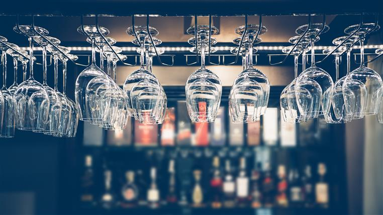 Wine glasses hanging from rack above bar.
