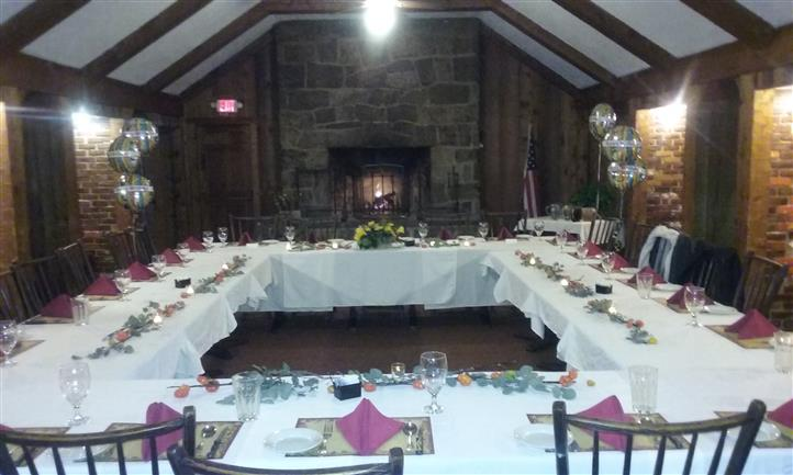 Tables set for dinner in a square shape and decarated with candles, and a fire place at the back