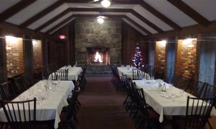 Restaurant hall decorated with string lights and a Christmas tree, with a fire place at the back