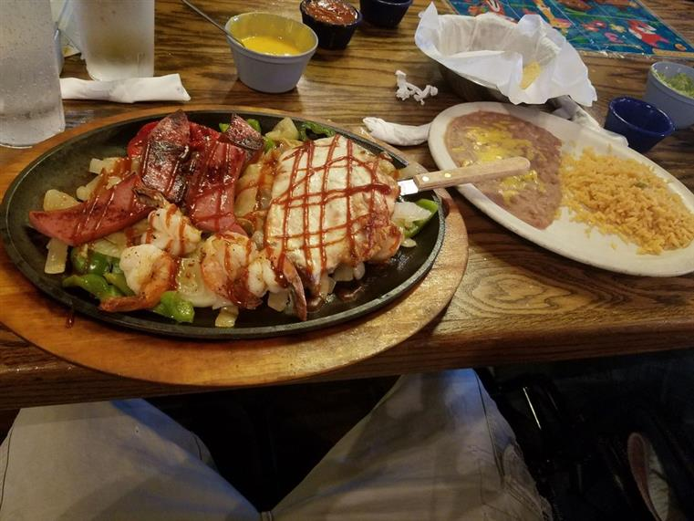 Big skillet with Mexican dish served over a bed of vegetables and served with side of sauce and rice