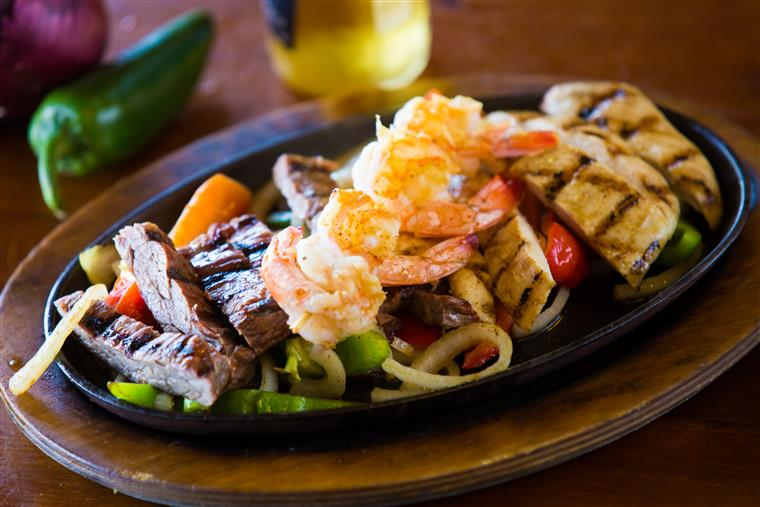 Steak. shrimp and chicken fajitas over vegetables