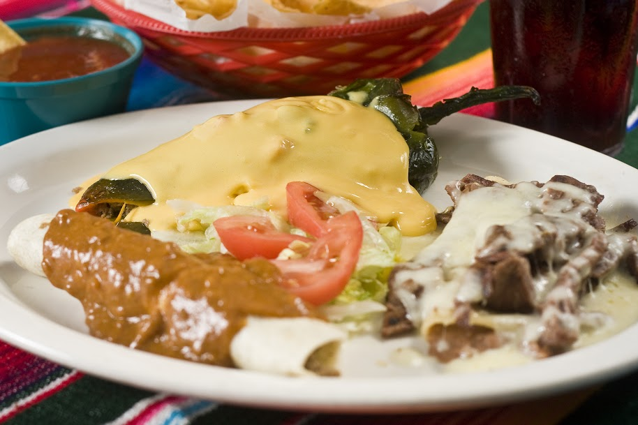 Combination of Mexican dishes served in a plate topped with sauces and served with garnish