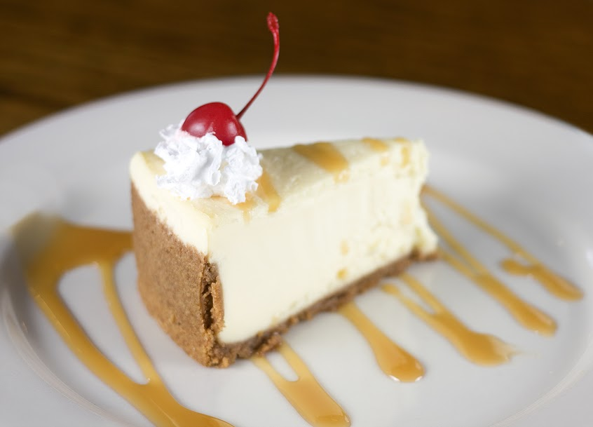 A slice of cheesecake with drizzled caramel and topped with whipped cream and a cherry