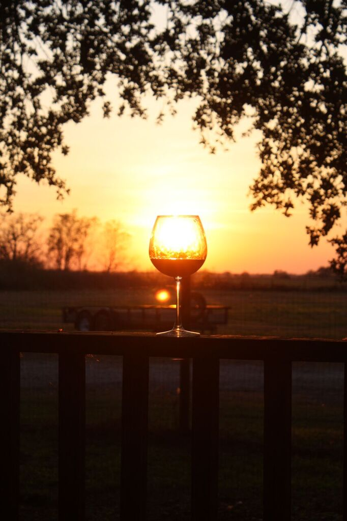 glass of wine displayed outdoors during a sunset