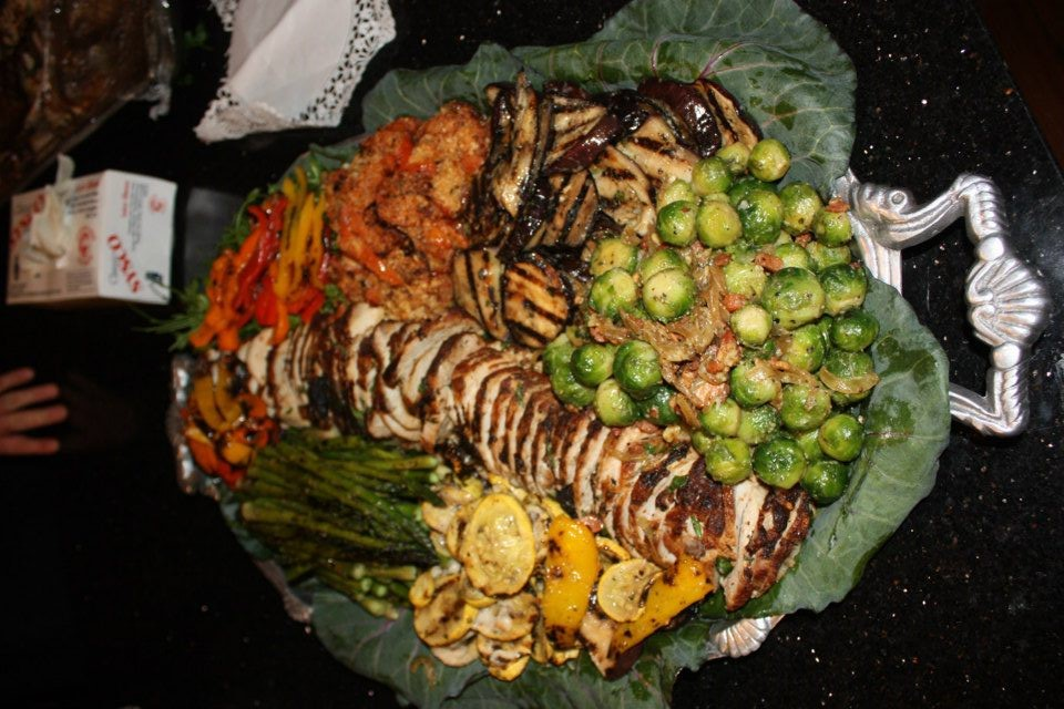 catering display of sliced chicken, brussel sprouts, peppers and other sliced vegetables
