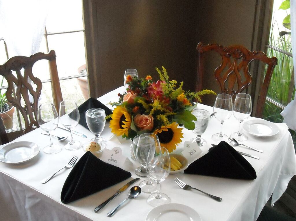 square table setup with with chairs, glassware, utensils and floral decorations.