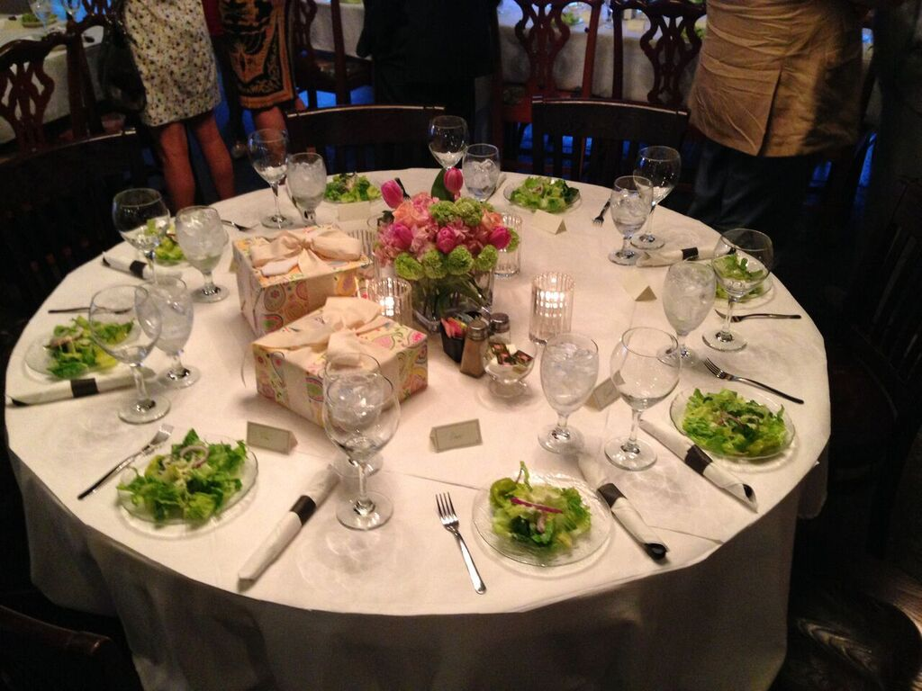 circular table setup with chairs, glassware, utensils and floral decorations.