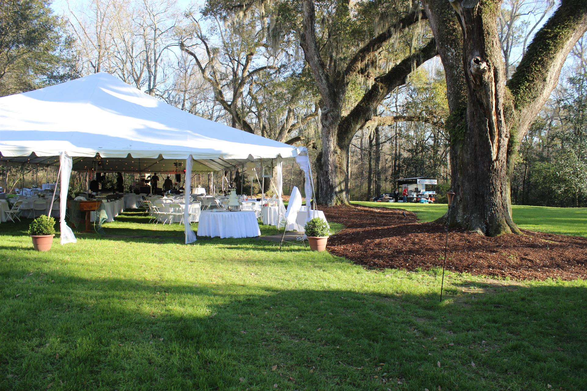 large tent set up wih tables and chairs set up underneath next to a tree