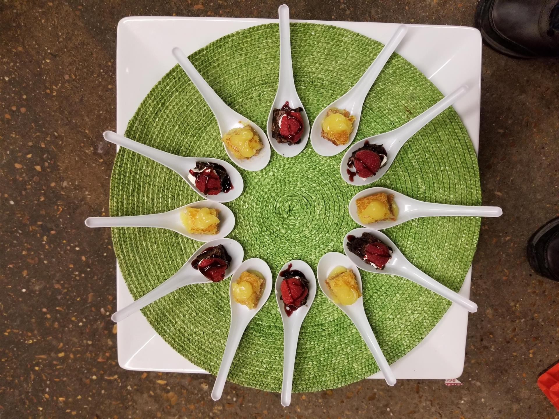 several spoons arranged in a circle with desserts on them