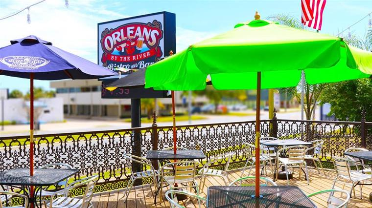 Outdoor seating with tables with umbrellas and chairs. Orleans by the river bistro and bar sign in background.