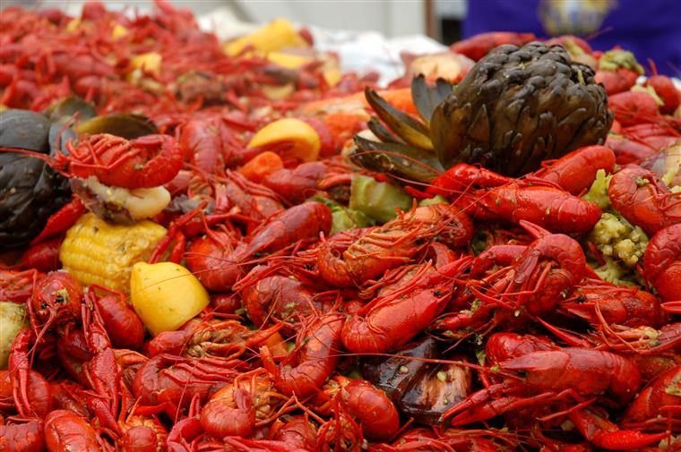 Huge pile of cooked crawfish with corn and lemons