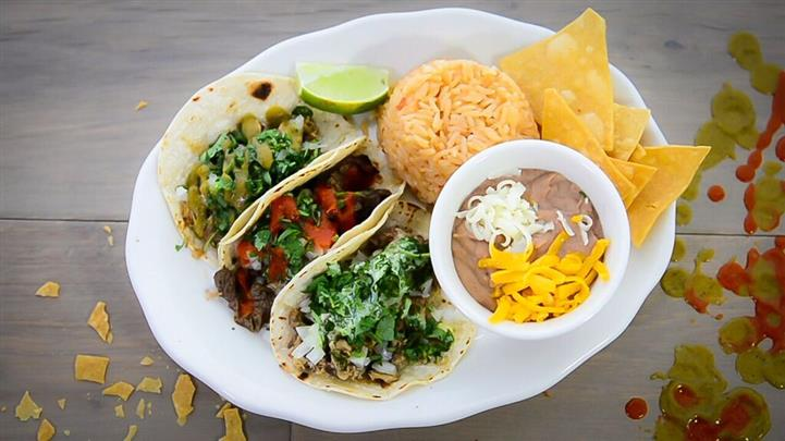 A dish of three tacos, served with tortilla chips, a bowl of dipping sauce, rice pilaf and a slice of lime