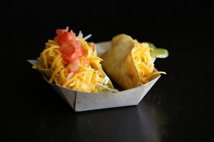 Two street tacos served with shredded cheddar cheese in a paper food container