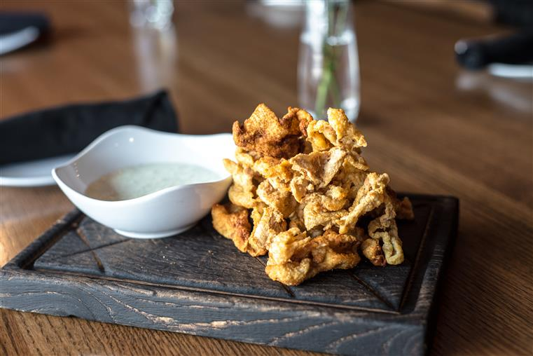 Chicken skins with buttermilk chive dip on rustic wood block