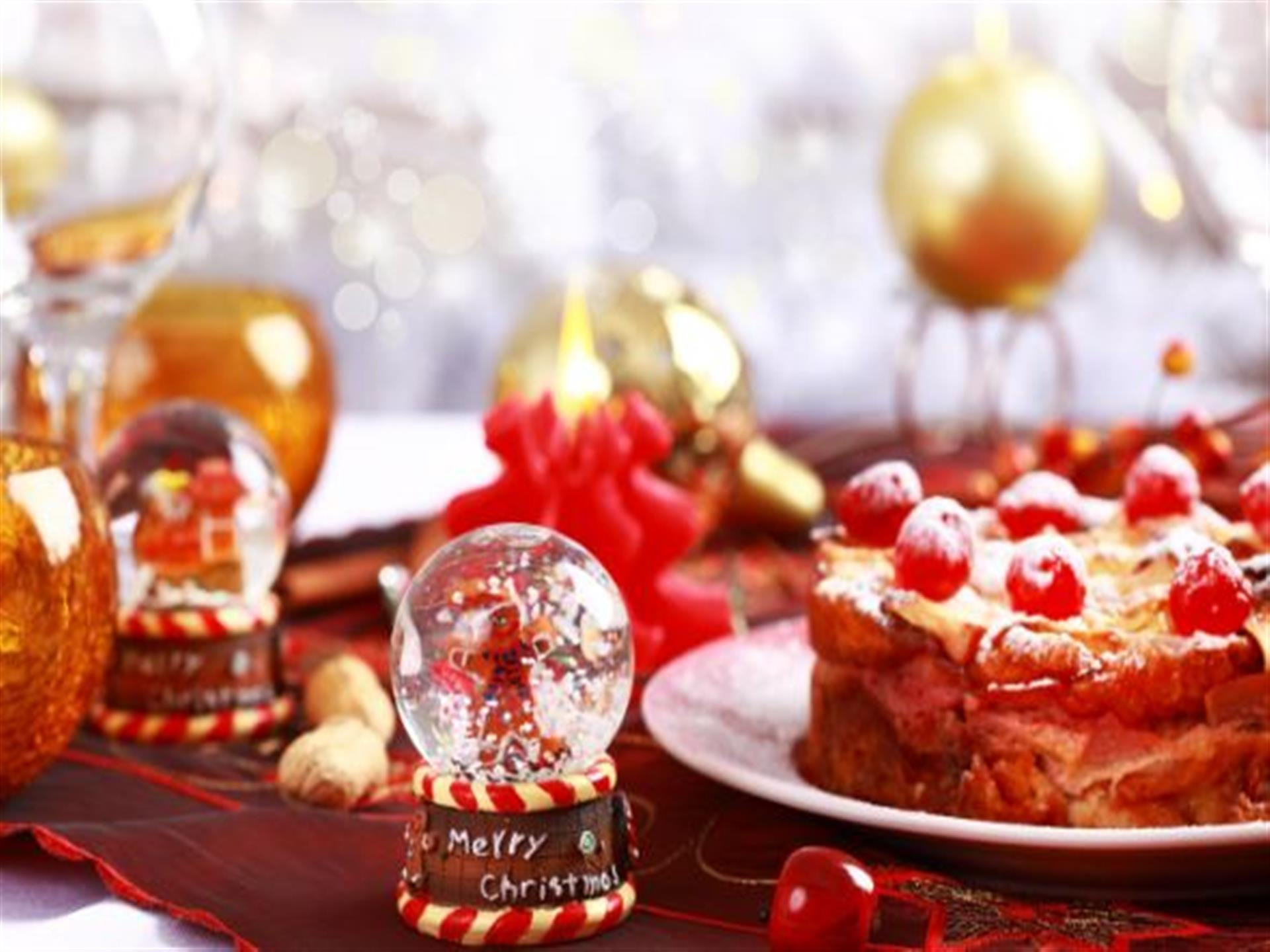 Festive holiday table with snowglobes and a cake.