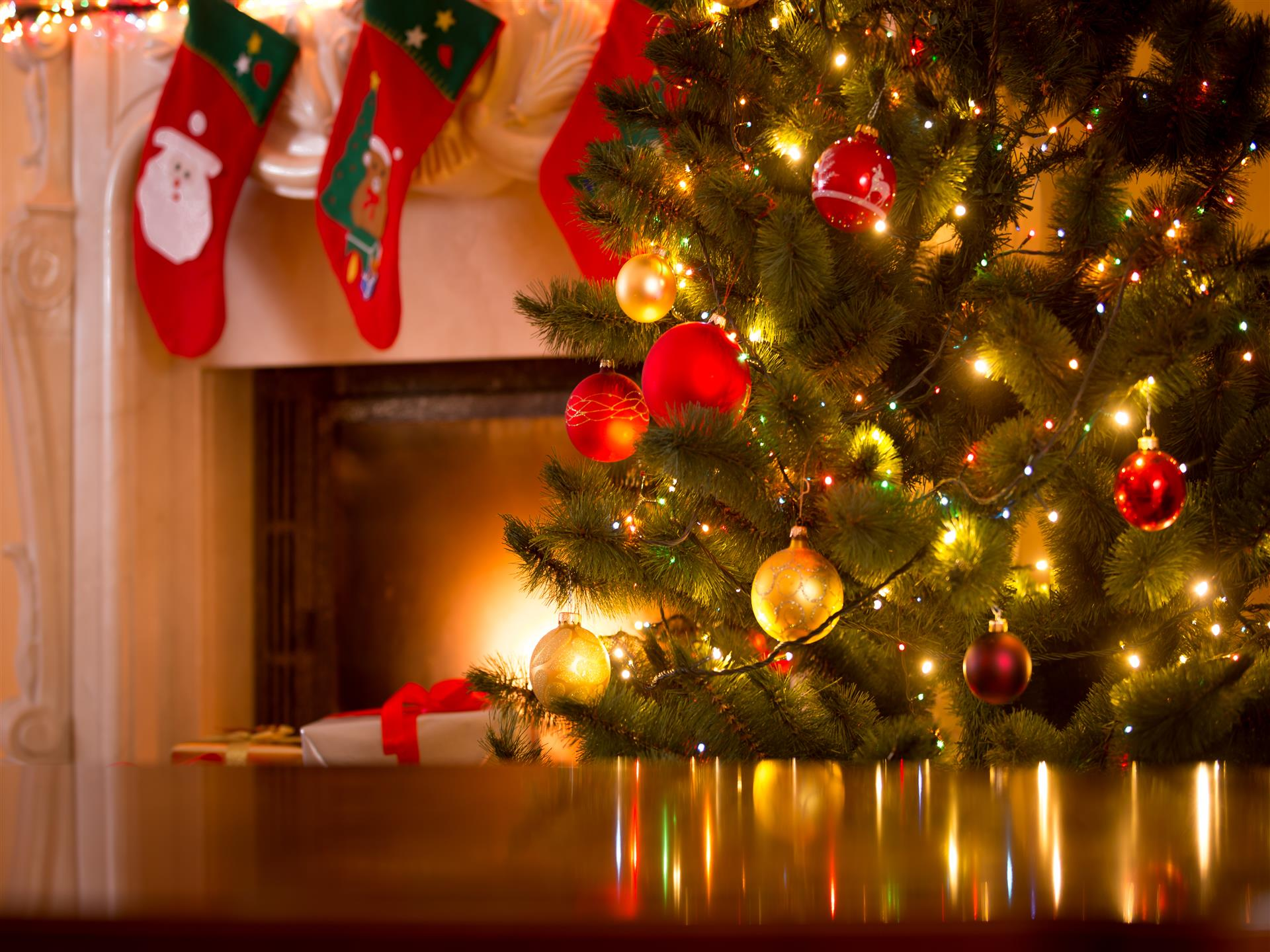 Christmas tree with a fireplace mantle in the background with stockings hanging.