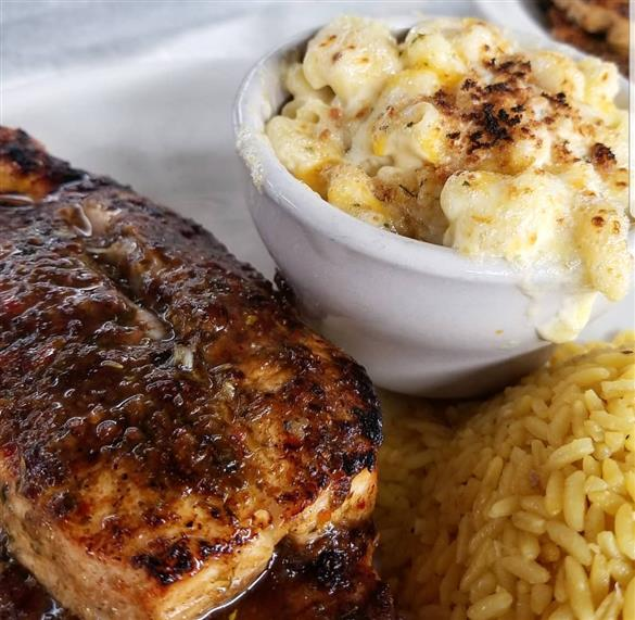 seasoned grilled chicken on a plate with rice and mac and cheese on the side.