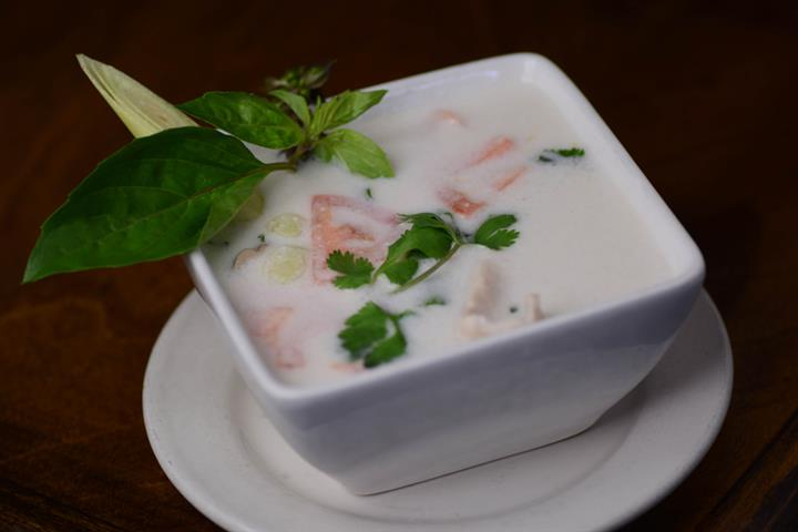 "Tom Kha ""Country"" soup made with sliced chicken breast, tomato, straw mushroom in a savory coconut milk, with crushed chili peppers, kha, cilantro, and lime juice."