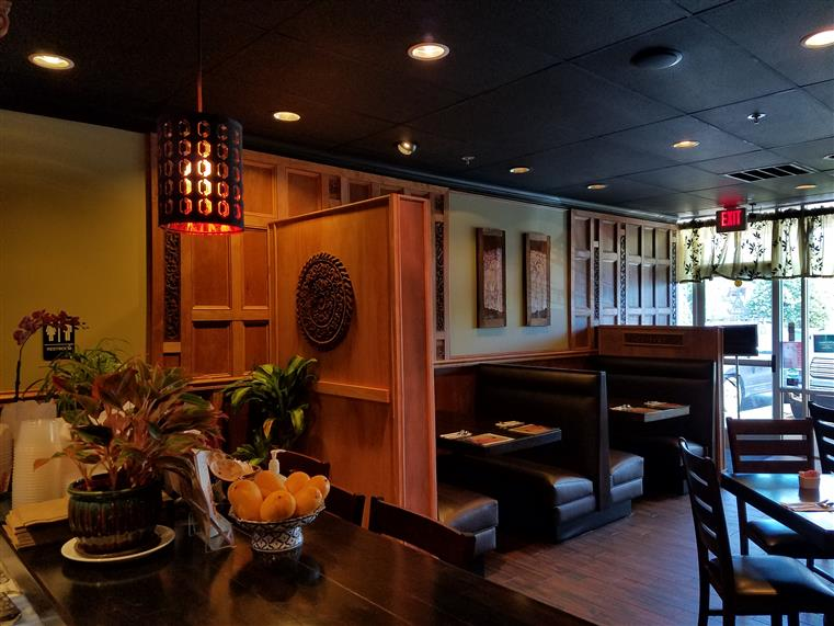 inside view of thai house with booths and tables