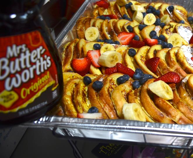 French toast in a tray with blueberries and strawberries