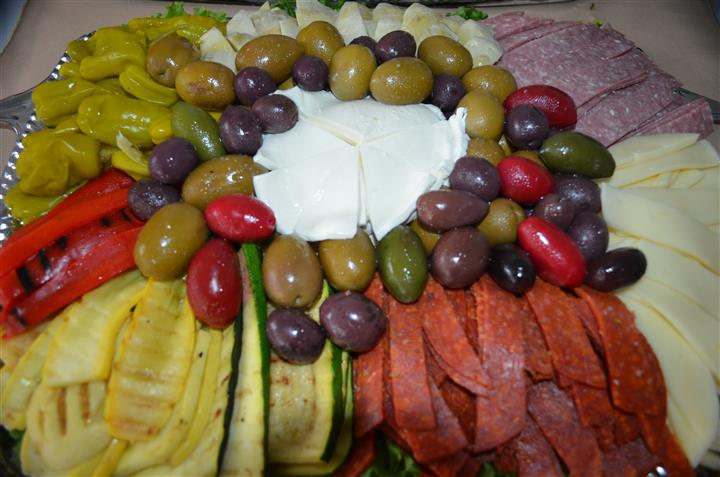 Meats, and vegetables with dipping sauce in the center