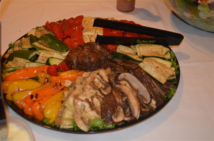 Platter filled with meats, vegetables, and cheeses