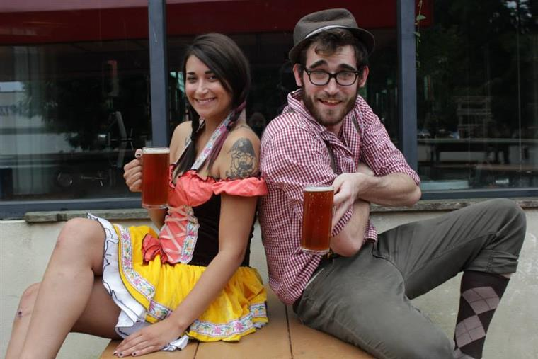 Young woman and young man dressed in german clothes holding full beer steins