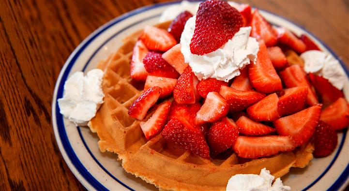 Waffles topped with diced strawberries and whipped cream