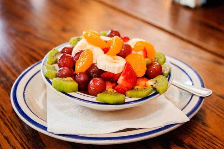 Fruit bowl with diced fruit like bananas, kiwis, grapes and more