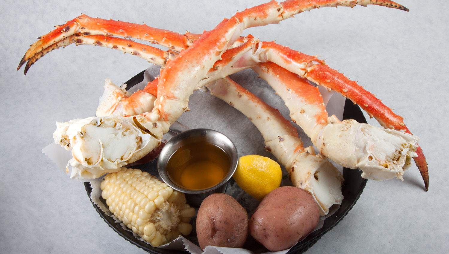 crab legs, corn on the cob, roasted potatoes, dipping sauce