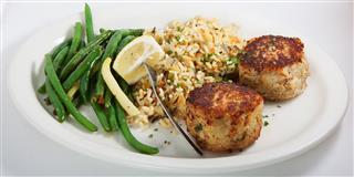 two crab cakes, rice and green beans
