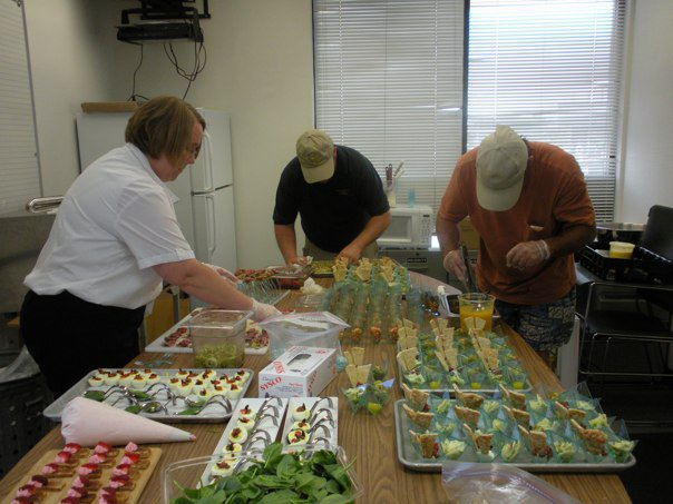 Two men and a women from the Chesapeake Bay Catering team working on food trays