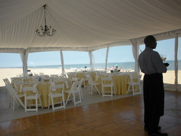 White round tables and sets with golden table cloths under a tent by the sea