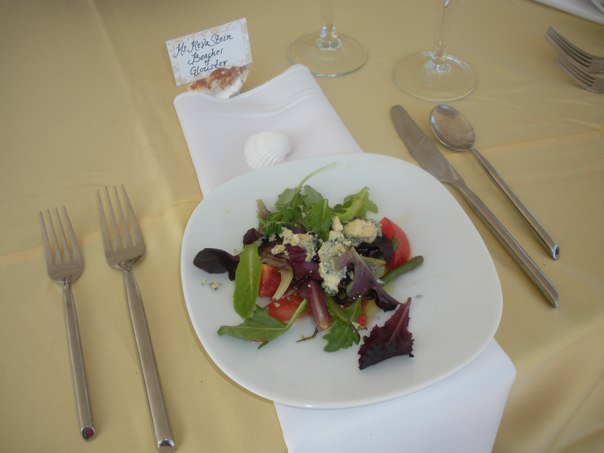 A salad with tomatoes, mixed greens and blue cheese crumbles