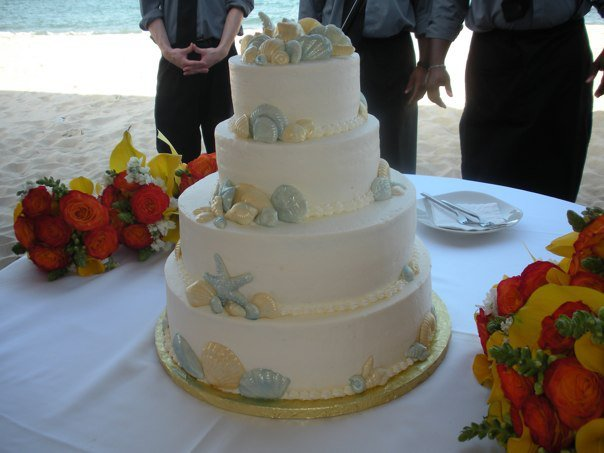 A four level wedfing cake decorated with several sea shells