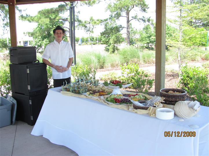 A young man standing by a white buffet with trays