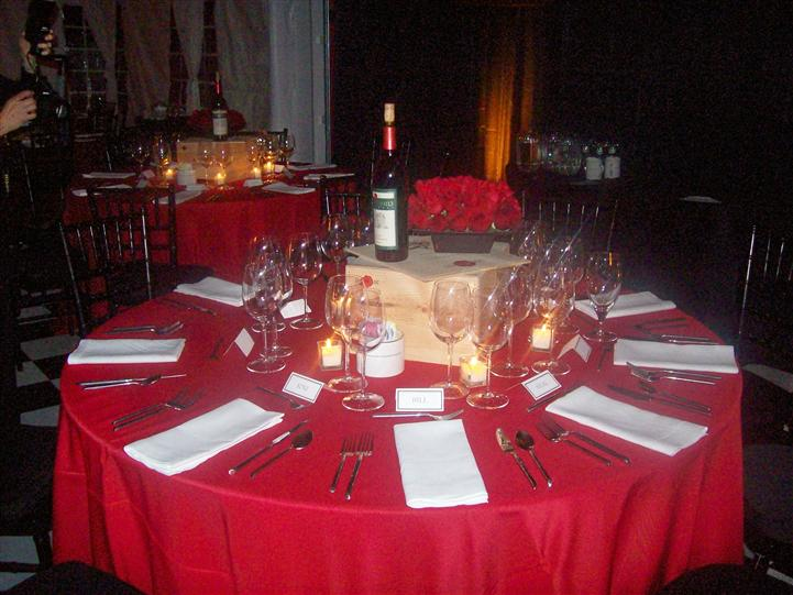 A round table with light red table cloth and white napkins