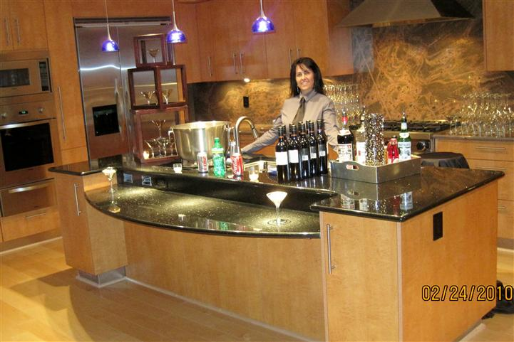 A server behind a bar buffet posing for a photo