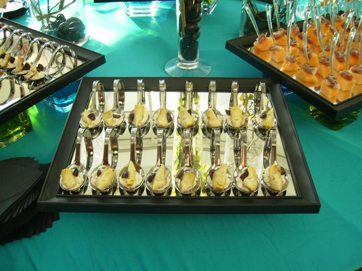 A tray of spoons with bites on a buffet