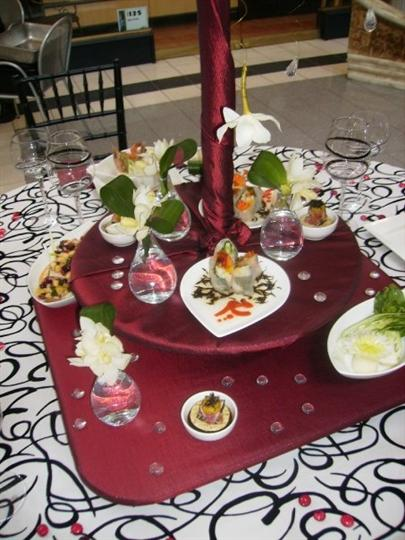 serveral appetizer platters on a decorated round table with black and white table cloth