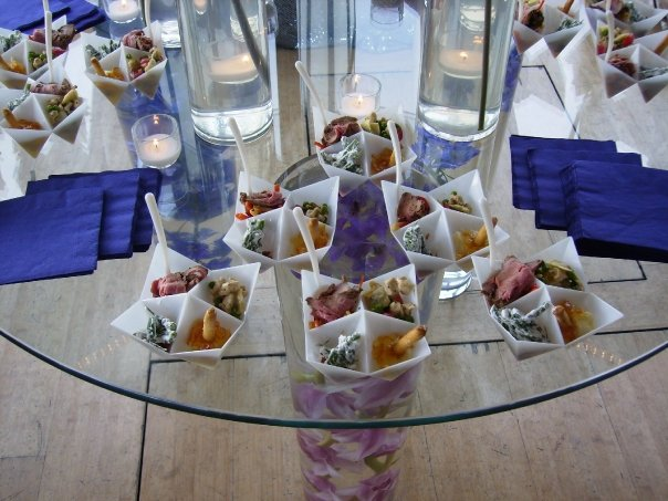 Modern geometric plates with four appetizers on a glass table