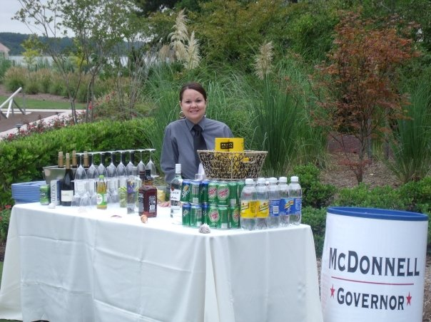 A server posing at an outdoor beverage buffet