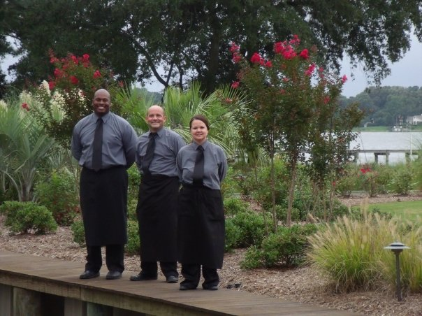 Three servers posing for a photo at a garden