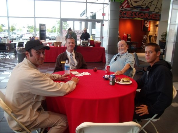 Four men at a round table with red table cloth posing for a photo
