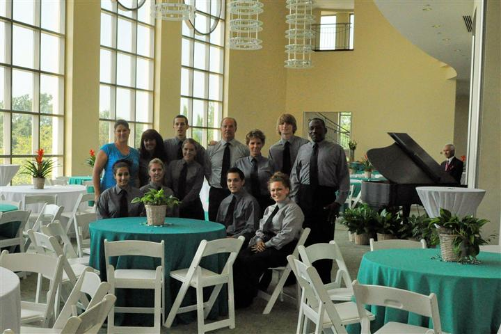 The servers in the light blue and whtie decorated hall posing for a photo