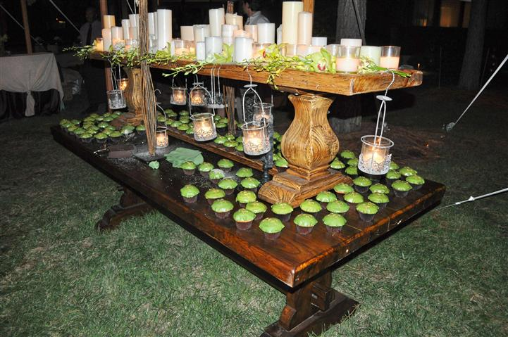 A wooden buffet with white candles and green cupcakes
