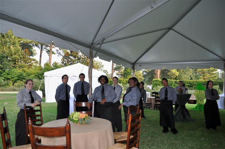 The servers posing for a photo under a tent